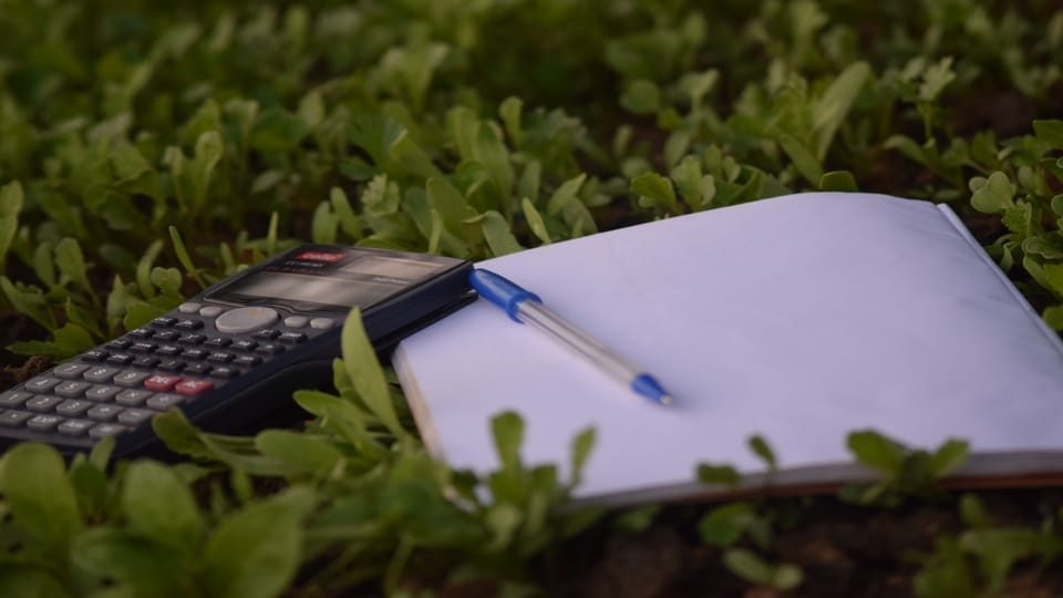 calculator-pen-notebook-in-grass