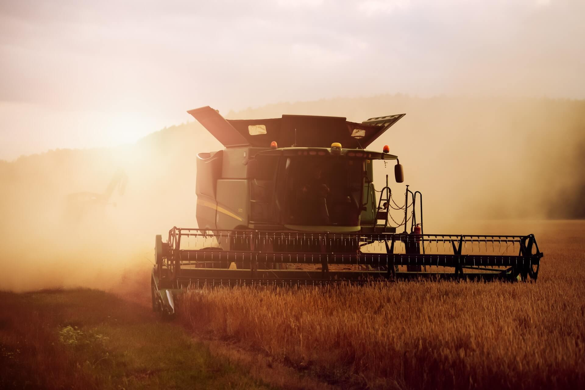 combine-harvesting-wheat-at-sunset