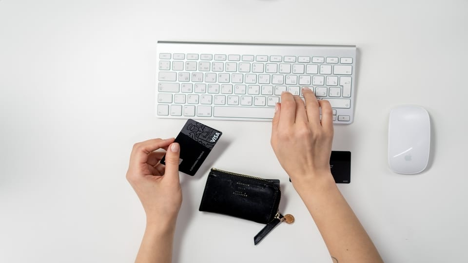 person-holding-credit-card-using-keyboard