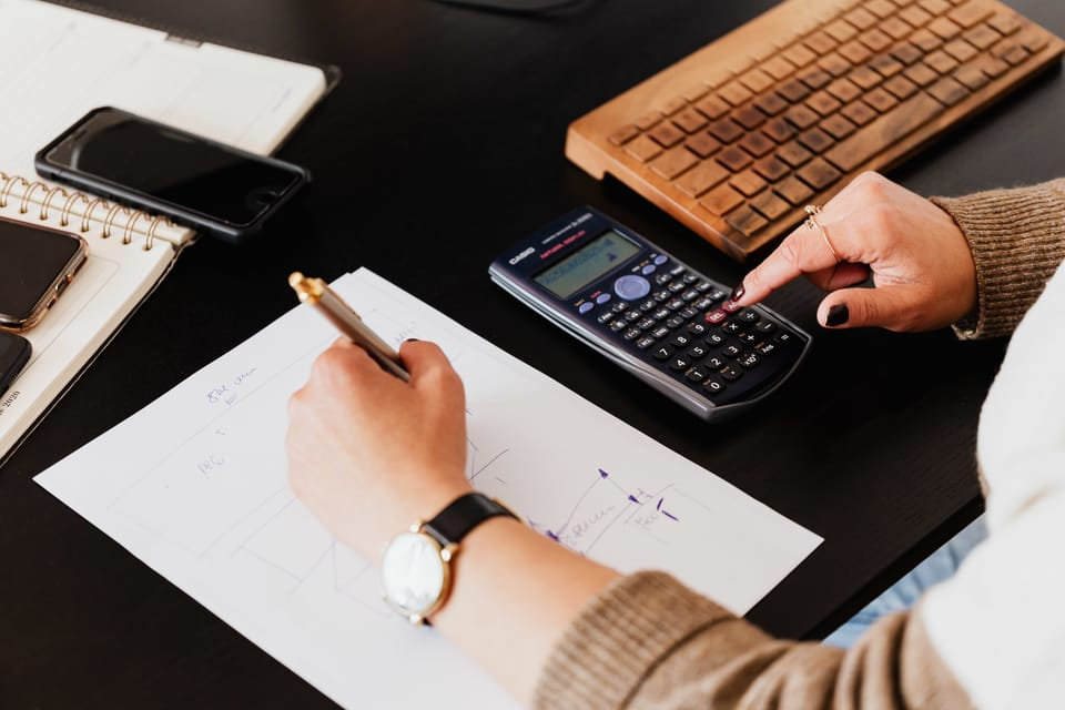 woman-using-calculator-and-taking-notes-on-paper